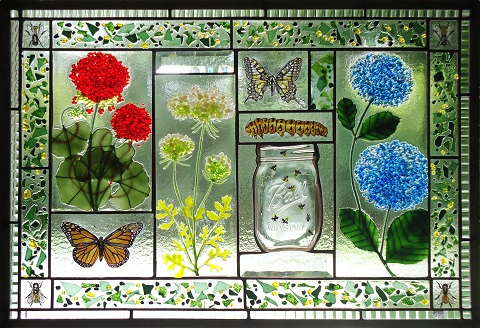 """Karen and Geoffrey Caldwell have taken the tradition of stained glass windows and infused it with new life. Their """"patchwork"""" fused, beveled and painted glass window panels are a naturalist's vision of the Maine Coast, the Hudson River and the Jersey Shore. Geoffrey paints with a 13th century technique of silver stain to bring insects, birds and sea creatures to life. Karen creates three-dimensional botanicals using modern methods in fused glass. The airy geometry of the stained glass brings it all together. In this piece, """"Summer"""", special elements are created like the 'jeweled confetti' border using glass and frit and taking it to a tack firing."""